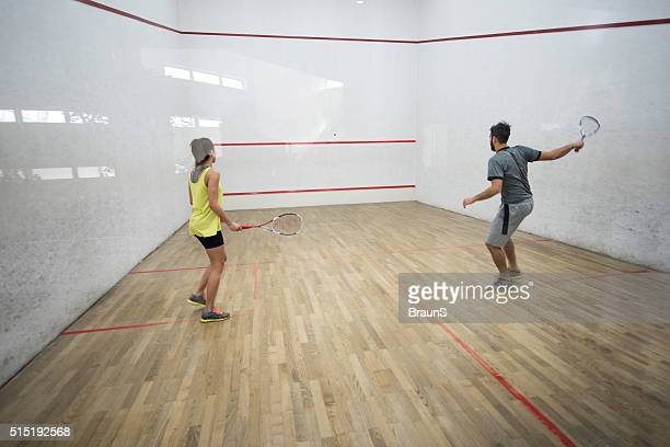 Back view of athletes playing racketball on a court.