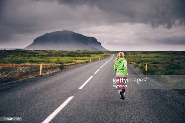 back view of athletic woman running on an empty road at iceland. - empty road stock pictures, royalty-free photos & images