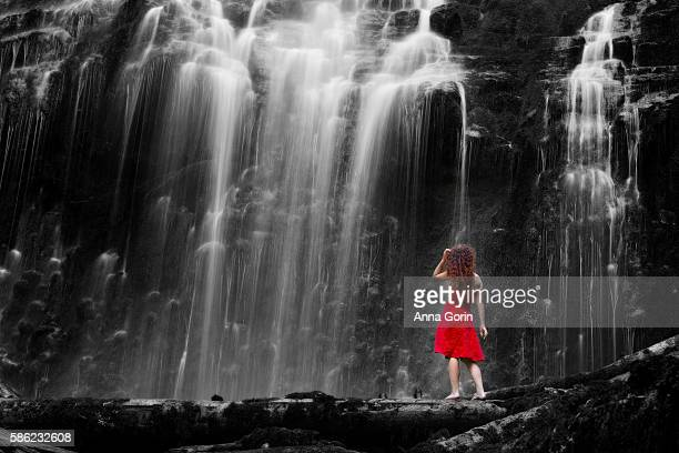 Back view of barefoot woman in red dress standing at base of waterfall, long exposure with isolated color