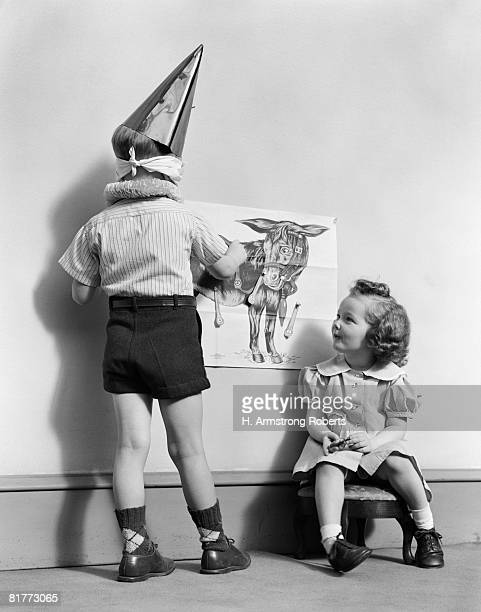 back view of blindfolded boy in dunce hat shorts & argyll socks pining the tail on the donkey front view of girl sitting on stool watching game fun. - dunce's hat stock pictures, royalty-free photos & images