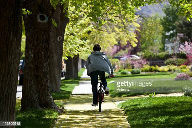 Back view of boy on footpath riding bike