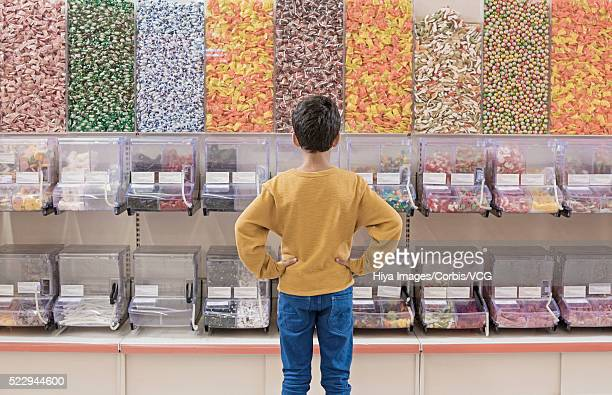 Back view of boy standing in candy store
