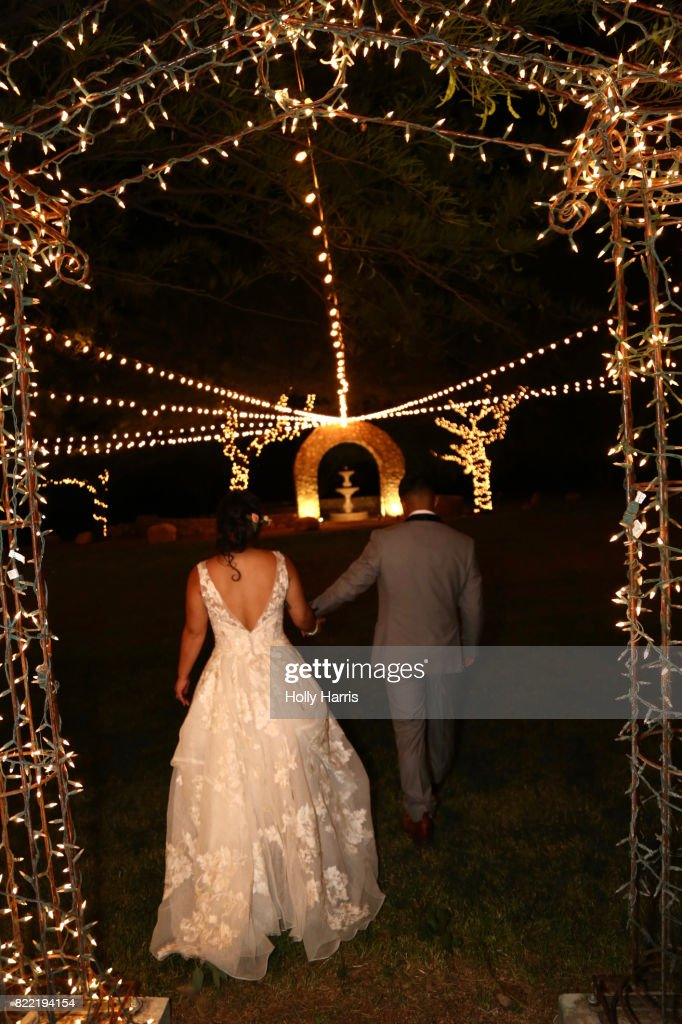 Back view of bride and groom holding hands and walking at night, illuminated garden : Stock Photo