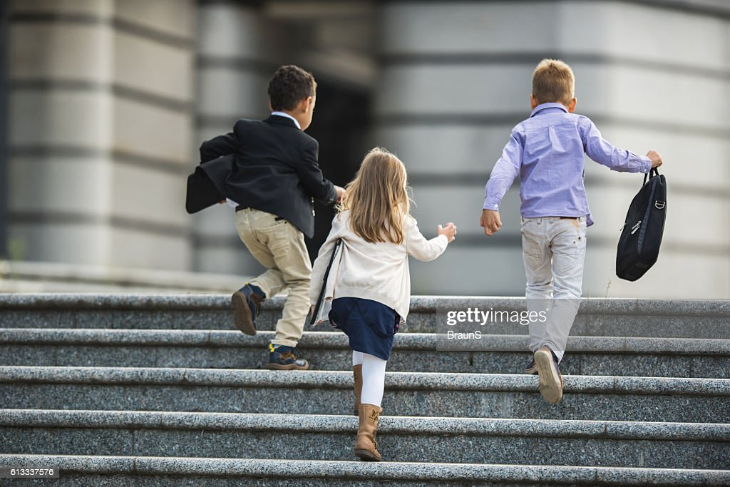 Back view of business kids running up the stairs. : Stock Photo