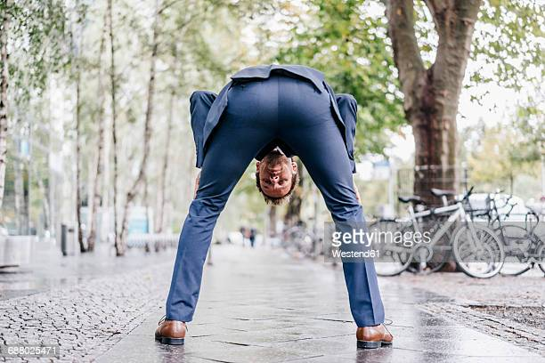back view of businessman bending over on pavement looking through his legs - bending over stock pictures, royalty-free photos & images