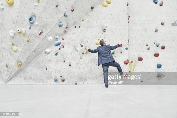 Back view of businessman standing in front of climbing wall in a bouldering hall