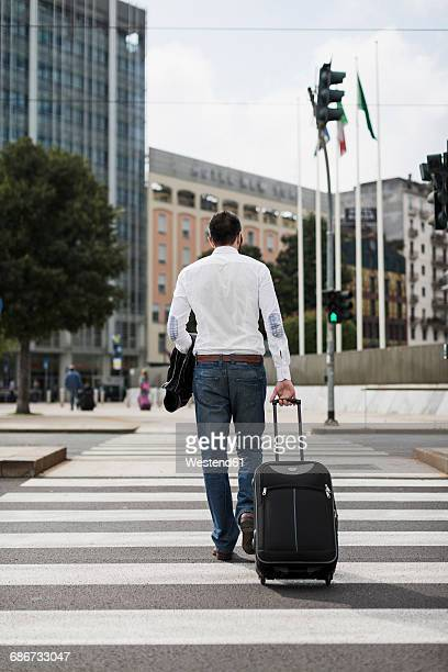 back view of businessman with suitcase crossing the street - wheeled luggage stock photos and pictures
