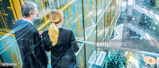 Back view of businesswoman and businessman in glass office corridor