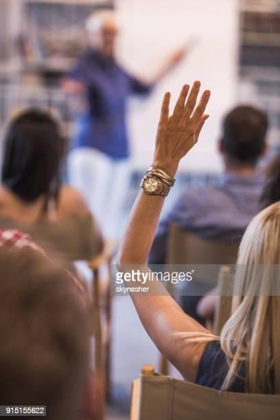 rückansicht des geschäftsfrau heben ihren arm auf kurs in einen sitzungssaal. - teilnehmen stock-fotos und bilder