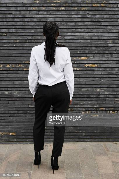 Back view of businesswoman with dreadlocks wearing white shirt and black trousers