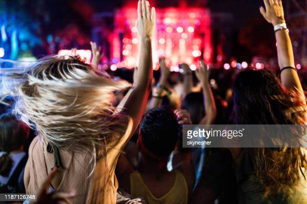 back view of carefree people dancing on music concert by night. - popular music concert stock pictures, royalty-free photos & images