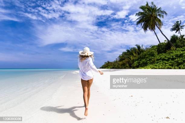 achtermening van zorgeloze vrouw in een overhemd dat op het strand loopt. - wit hemd stockfoto's en -beelden