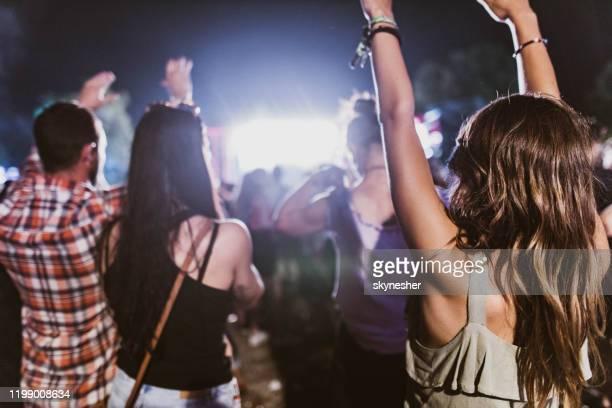 vista trasera de mujer despreocupada con las manos levantadas en un concierto. - festivalero fotografías e imágenes de stock