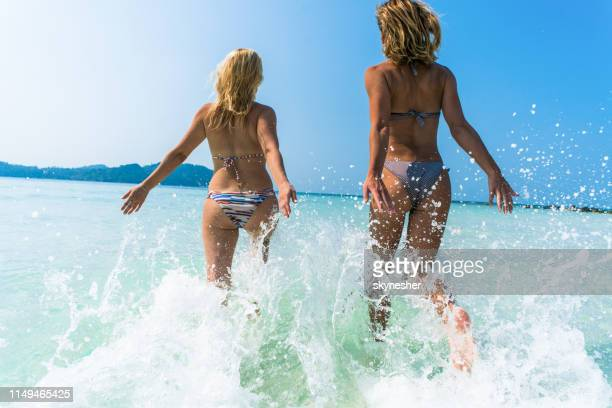 back view of carefree women having fun while running into the sea. - bikini stock pictures, royalty-free photos & images