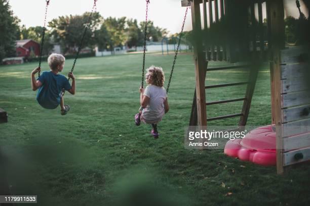 back view of children swinging - nur kinder stock-fotos und bilder