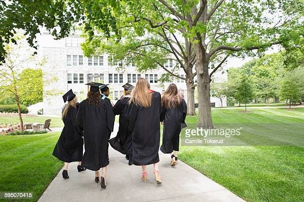 Back view of college graduates walking away