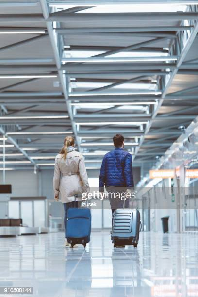 Back view of couple at airport terminal with suitcase