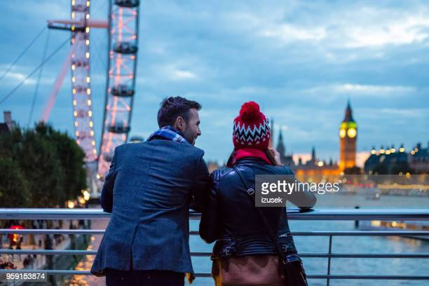 back view of couple in london in the evening - london england stock pictures, royalty-free photos & images