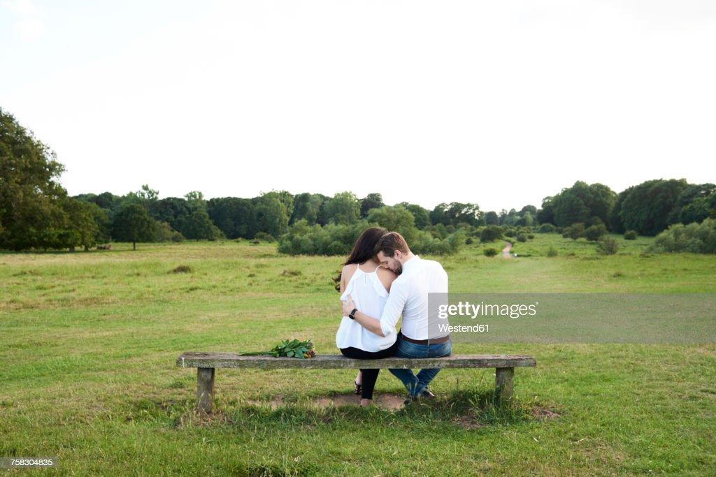 Back View Of Couple Sitting On A Bench In A Park Stock Photo Getty