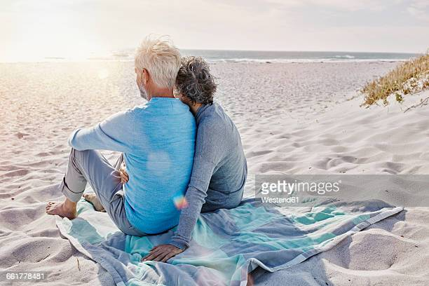 Back view of couple sitting on the beach looking to the sea