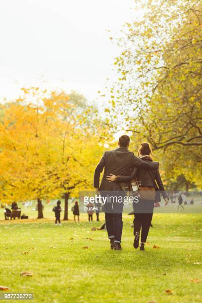 Back view of couple walking together in a public park