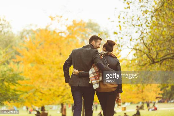 back view of couple walking together in a public park - izusek stock pictures, royalty-free photos & images