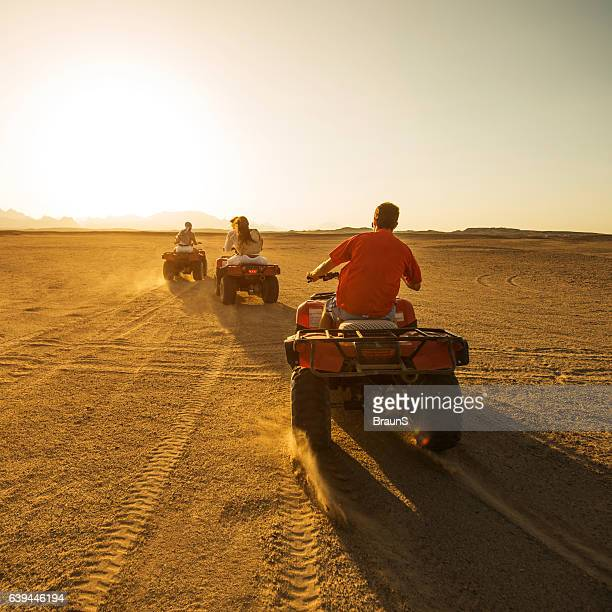 Back view of driving quad bikes at sunset!