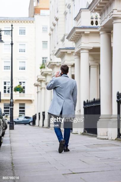 Back view of elegant man walking the sidewalk in the city