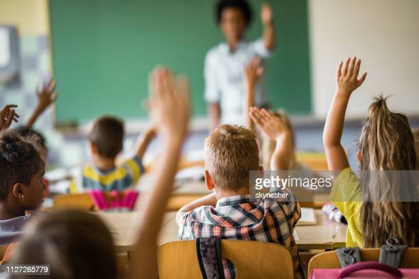 back view of elementary students raising their hands on a class. - hand raised stock pictures, royalty-free photos & images