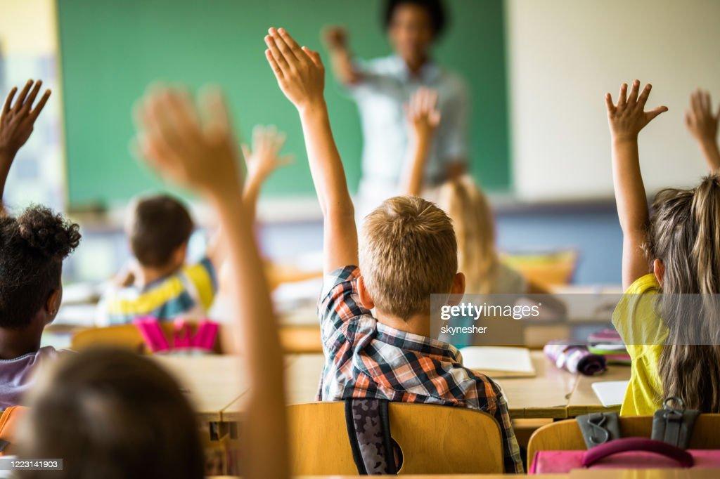 Achtermening van elementaire studenten die hun handen op een klasse opheffen. : Stockfoto