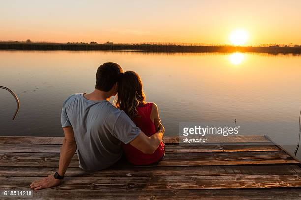 Back view of embraced couple enjoying at sunset by lake.