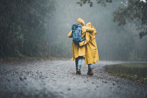 Back view of embraced couple in raincoats hiking on a rain. 1179778309