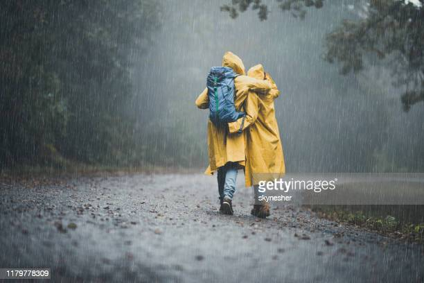 back view of embraced couple in raincoats hiking on a rain. - rain stock pictures, royalty-free photos & images