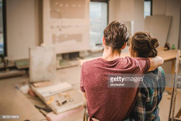 back view of embraced couple in their renovating apartment. - reform stock pictures, royalty-free photos & images