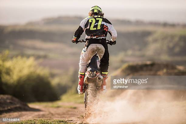 back view of enduro motocross rider on a dirt track. - motorcycle racing stock pictures, royalty-free photos & images