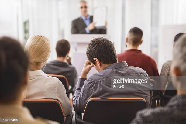 Back view of exhausted businessman attending an education event.