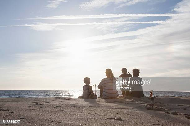Back view of familiy with two kids sitting on the beach at twilight