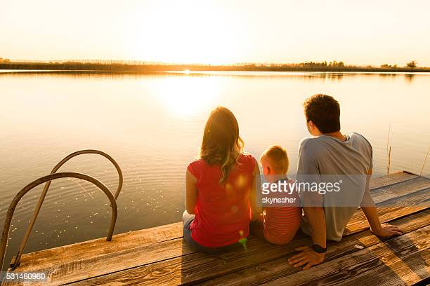 Back view of family relaxing on a pier at sunset.