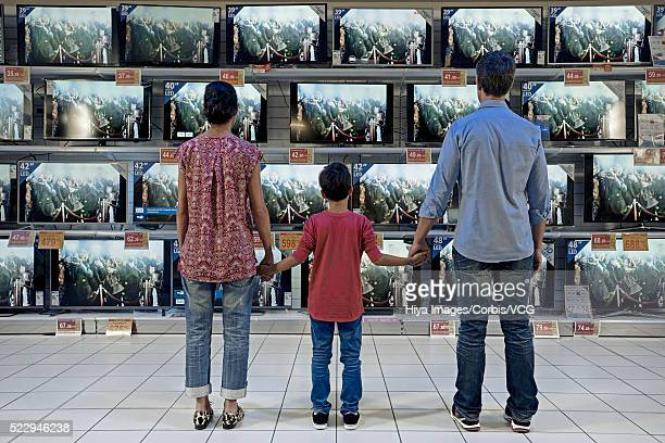 Back view of family standing in electronics store against flat panel televisions display