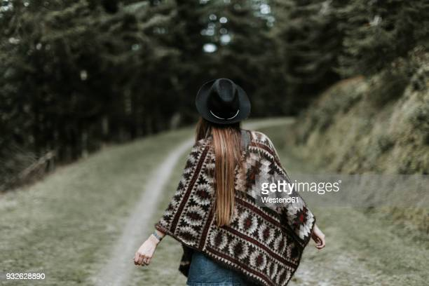 Back view of fashionable young woman wearing hat and poncho in nature