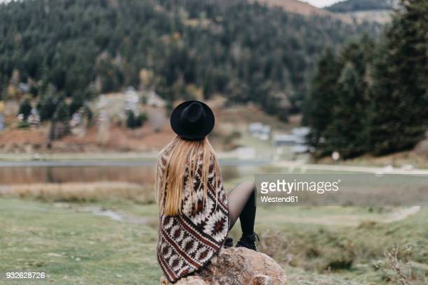back view of fashionable young woman wearing hat and poncho sitting on a rock - long nylon legs stock pictures, royalty-free photos & images