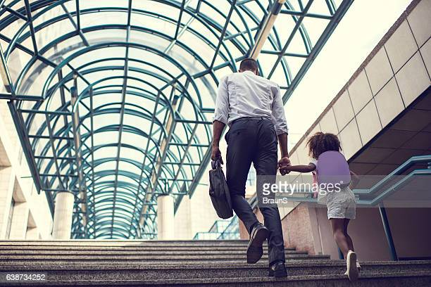 Back view of father and daughter walking up the stairs.