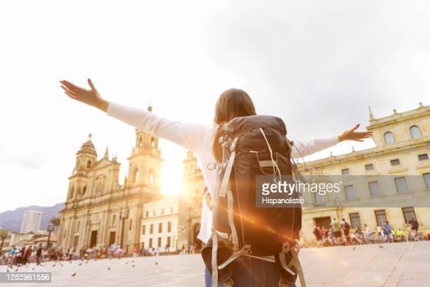 観光を楽しむ腕を伸ばした女性バックパッカーのバックビュー - ボゴタ ストックフォトと画像