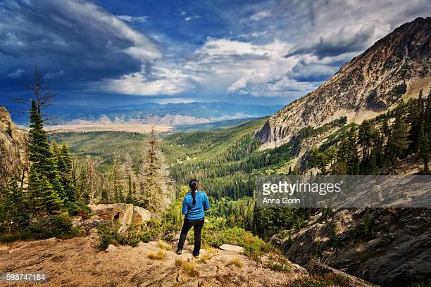 Back view of female hiker looking at valley far below along trail to Goat Lake in Sawtooth Mountains, Idaho