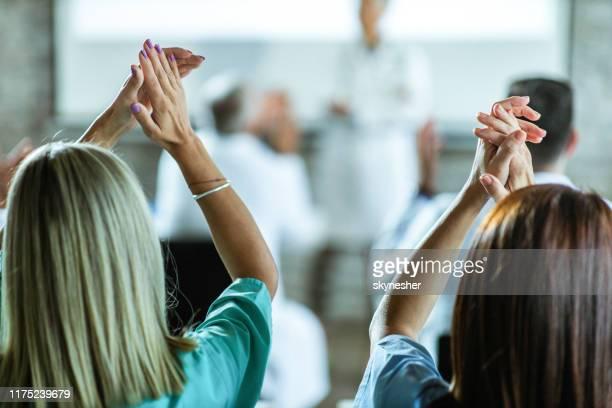 achteraanzicht van vrouwelijke verpleegkundigen applauloderen op medisch seminar in het kantoor. - in de handen klappen stockfoto's en -beelden