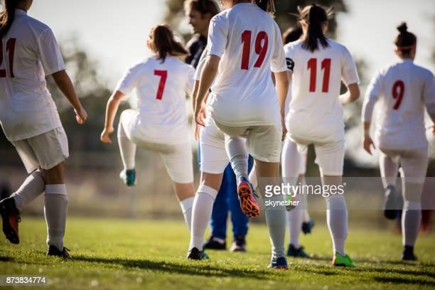vista trasera del equipo de fútbol femenino calentando antes del partido. - fútbol femenino fotografías e imágenes de stock