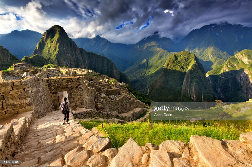 Back view of female tourist descending stairs overlooking Machu Picchu ruins at sunset, Peru : ストックフォト
