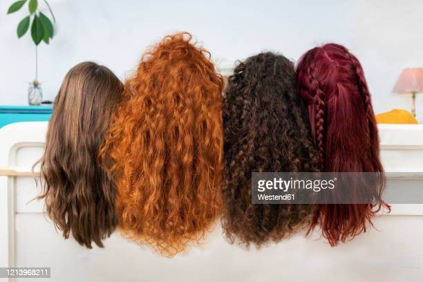 back view of four women with long brown and red hair - curly stock pictures, royalty-free photos & images