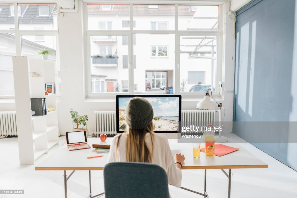 Back view of freelancer working at desk in a loft : Stock Photo