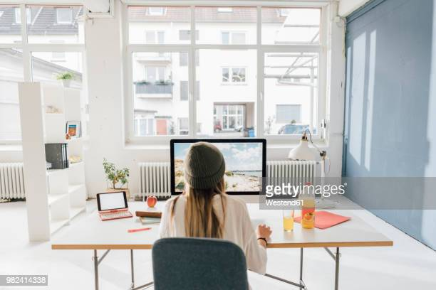 back view of freelancer working at desk in a loft - back to work stock pictures, royalty-free photos & images